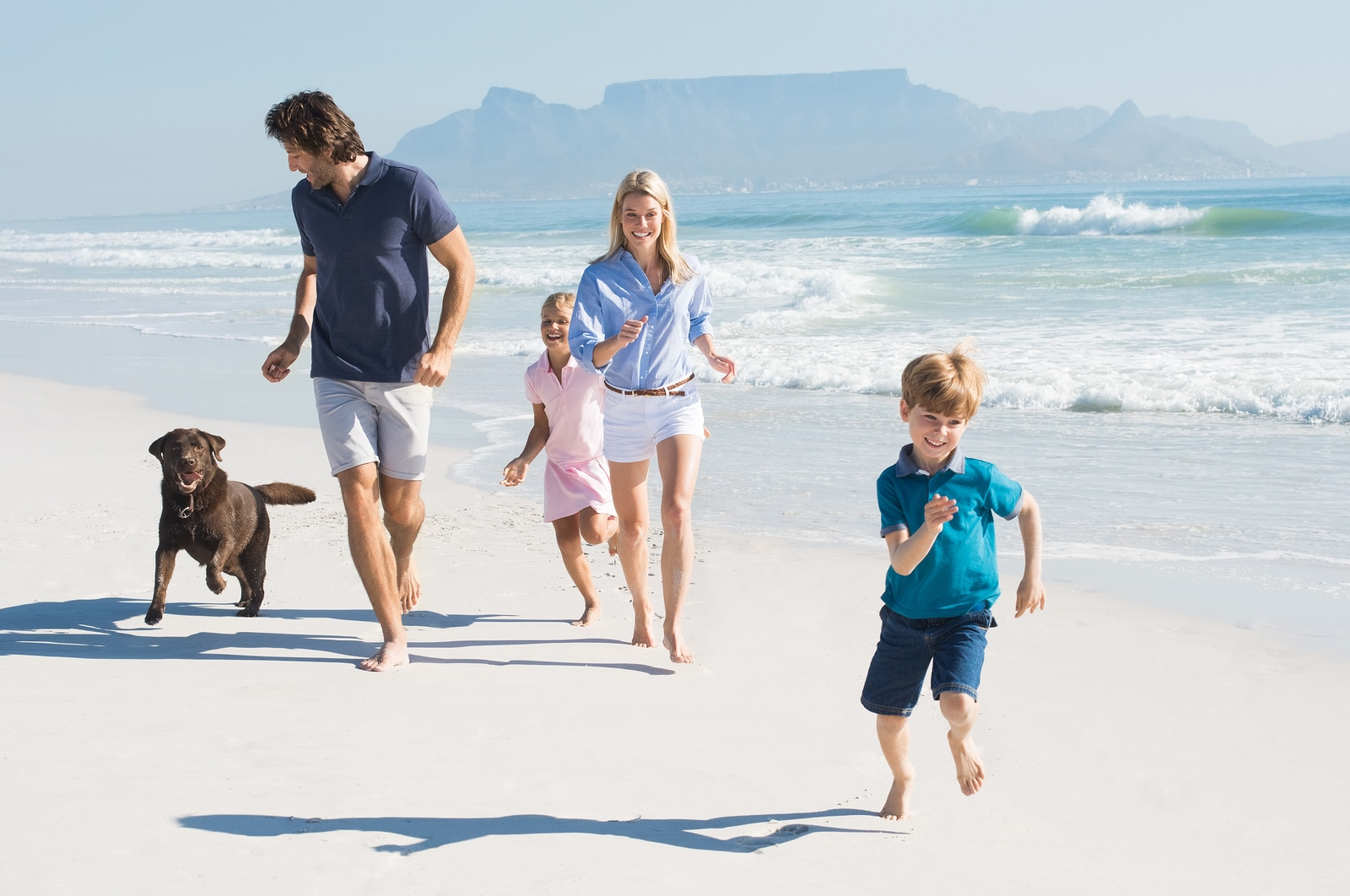 Family with two small children and brown dog running on the beach.